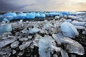 ISL0315_0153_Sea currents carry blocks of ice on the black beach in Jökulsárlón (Iceland)